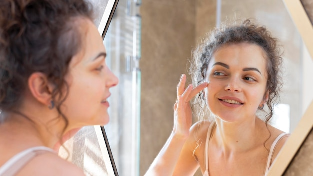 Woman looking in mirror and applying cream on face