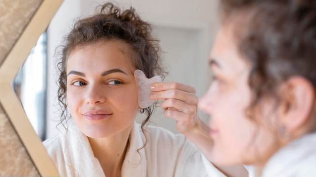 Woman looking in mirror and doing face massage