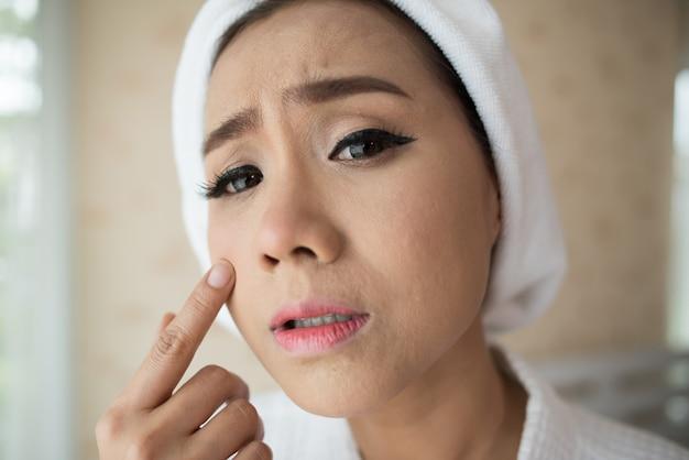 Donna guardando specchio a casa e controllando il suo viso