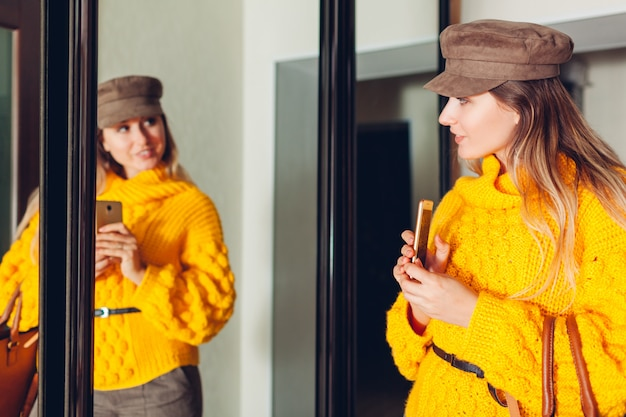 Woman looking at mirror at home wearing stylish sweater and accessories and taking selfie