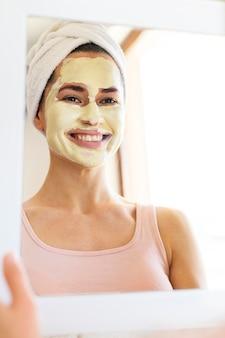 Donna che si guarda allo specchio mentre indossa la maschera
