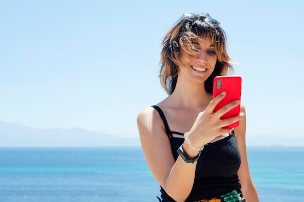 Woman looking at mobile phone with the sea in the background