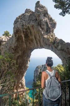 Woman looking to a natural arch. capri, italy