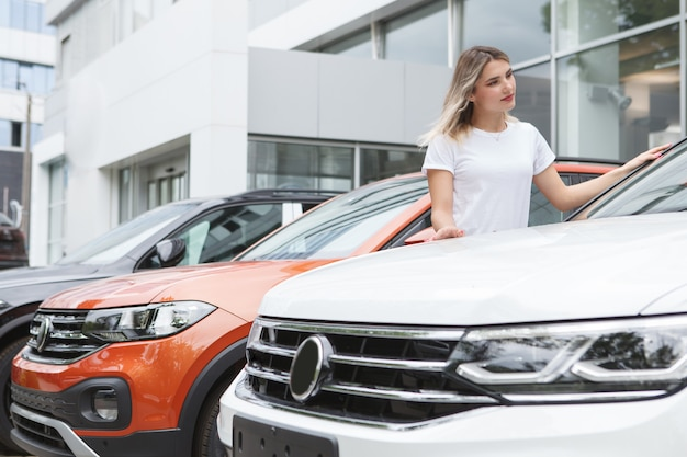 Woman looking at new suv car for sale at automobile dealership outdoors