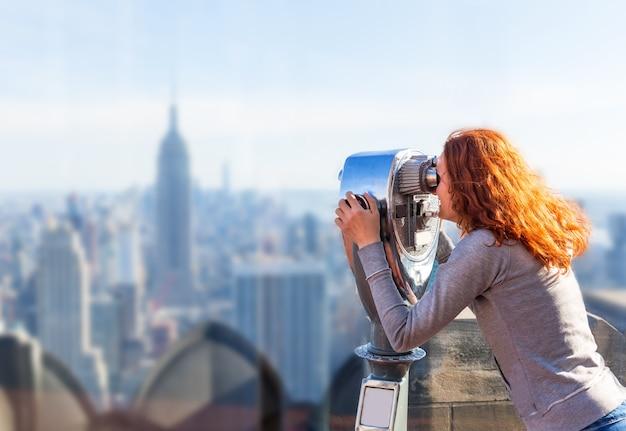Woman looking in observation binoculars.