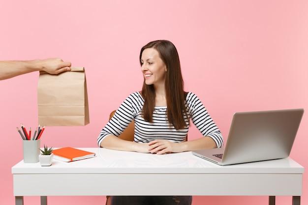 Женщина смотря на коричневый ясный пустой пустой бумажный мешок ремесла, работа на столе с компьтер-книжкой пк изолированной на розовой предпосылке. доставка продуктов курьерской службой из магазина или ресторана в офис. скопируйте пространство.