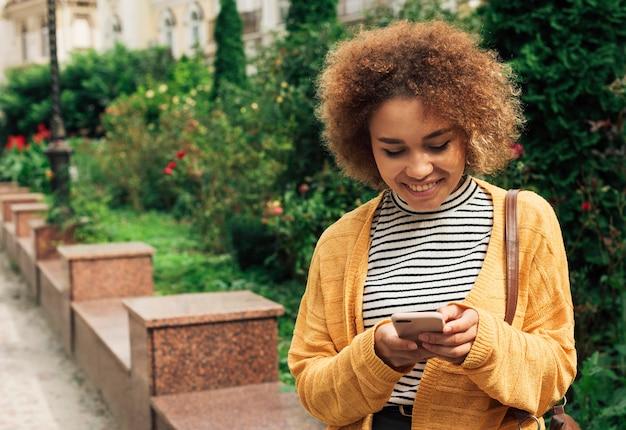 Женщина смотрит на свой телефон осенью