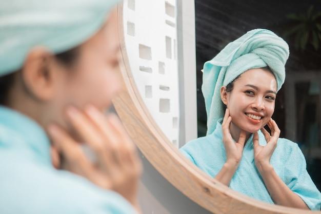 Женщина смотрит на отражение в зеркале с чистой свежей кожей, когда она в ванной
