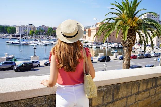 港とイタリア、バーリの街を見ている女性。背面図。