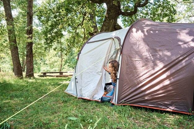 森の中で晴れた朝に観光テントの外を見ている女性