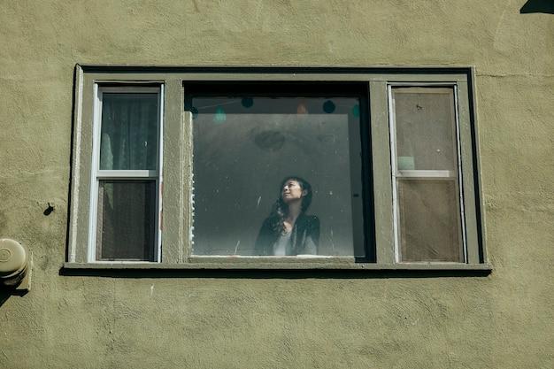 Женщина смотрит в окно своей квартиры в центре лос-анджелеса во время пандемии covid-19