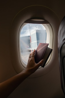 Woman looking out through window of the airplane and show passport