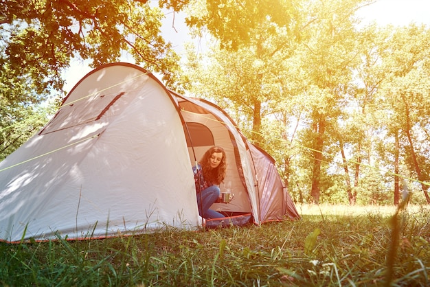 Woman looking out of tourist tent on sunny morning in forest