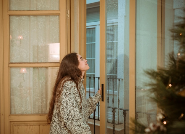 Woman looking out of window next to christmas tree