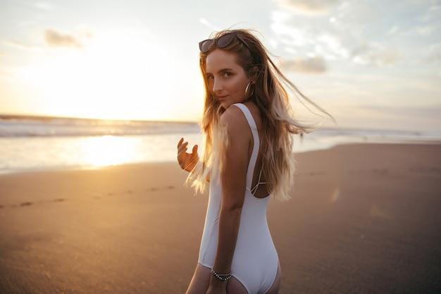 空の背景にポーズをとっている間、肩越しに見ている女性。海岸で身も凍るような白い水着の金髪の女性。