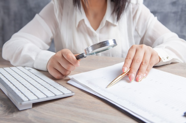 Woman looking at paper with a magnifying glass in front of a computer