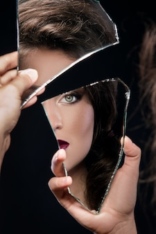 Woman looking in the piece of mirror