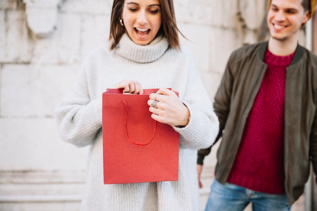 Woman looking at present from man
