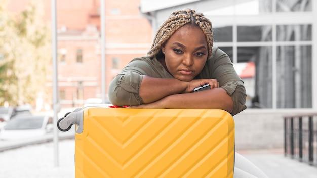 Donna che sembra triste mentre resta sul suo bagaglio
