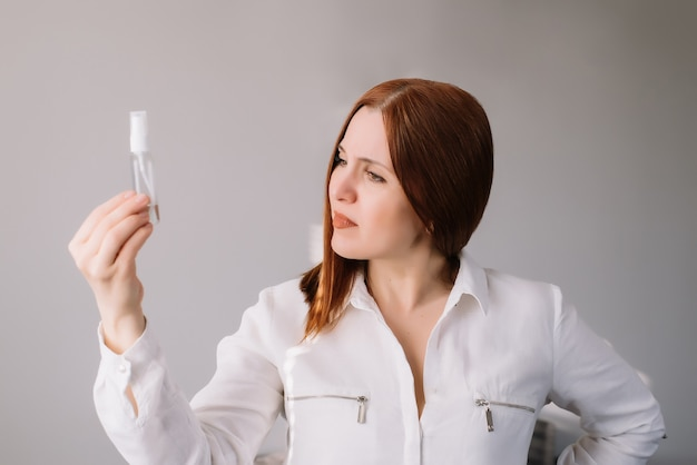 Woman looking at the sanitizes gel at home. woman uses an antibacterial hand cleaner.