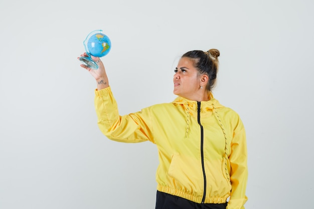 Woman looking at school globe in sport suit and looking hopeful , front view.