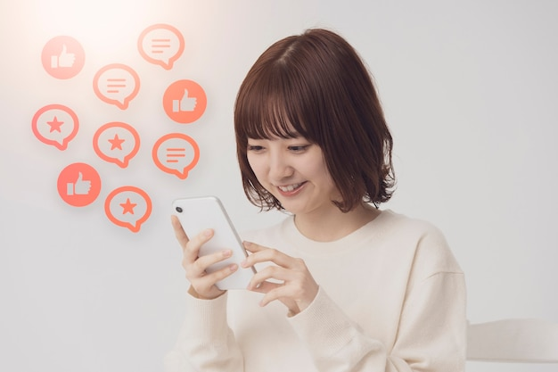 A woman looking at the screen of a smartphone and icons that imaged sns