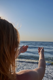 Woman looking to the sea ocean from the back naked with windy hair. the girl pulls her hands to the sea
