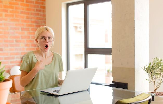 Женщина выглядит шокированной и удивленной с широко открытым ртом, указывая на себя