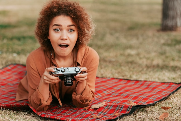 Woman looking shocked while holding a camera