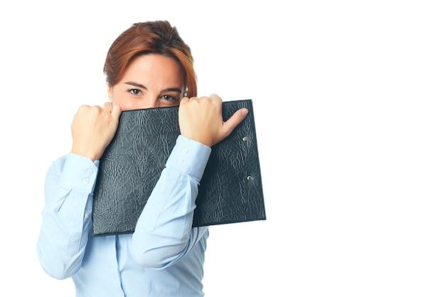 Woman looking shy behind a black folder