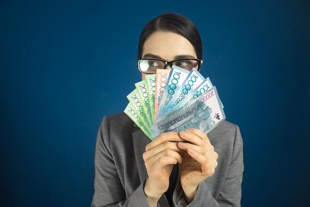 Женщина смотрит в сторону над казахстанскими деньгами тенге в руках.