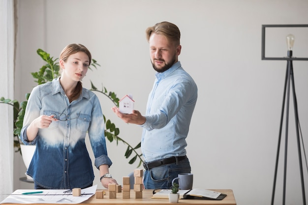Woman looking at small house model holding by her colleague at workplace