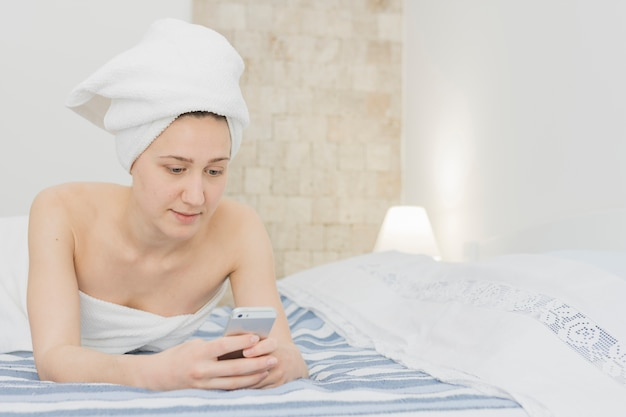 Woman looking at smartphone in bed after shower
