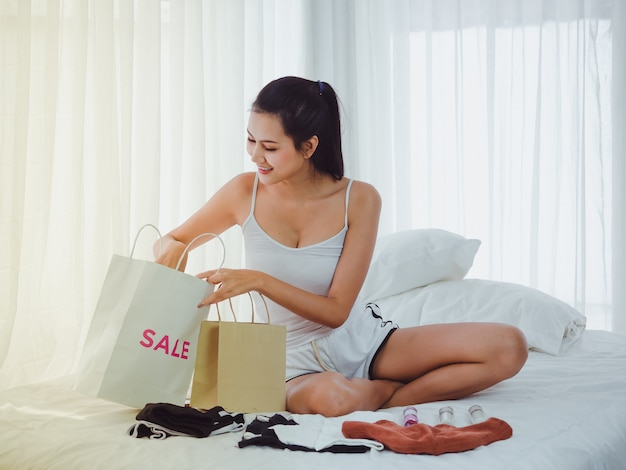 Woman looking for something in a shopping bag