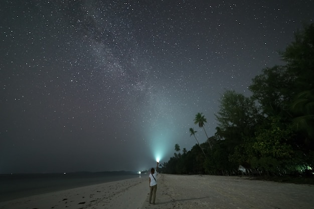 Woman looking at stars and milky way on sand beach