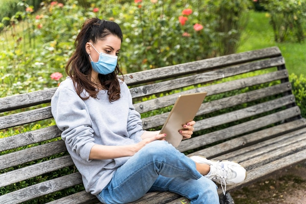 Woman looking at a tablet while wearing medical mask