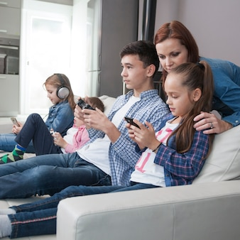 Woman looking at teenager and girl playing video games