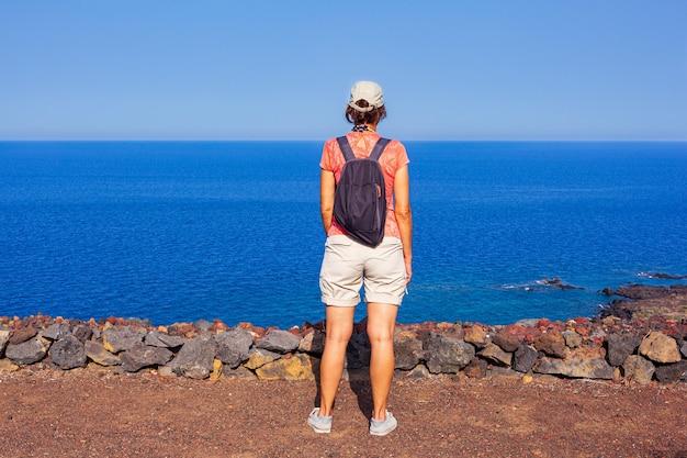リノザ島モンテネロと呼ばれる火山の頂上から海を見ている女性。シチリア。イタリア