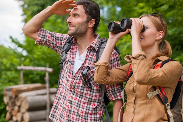 Woman looking through the binoculars. hiking time