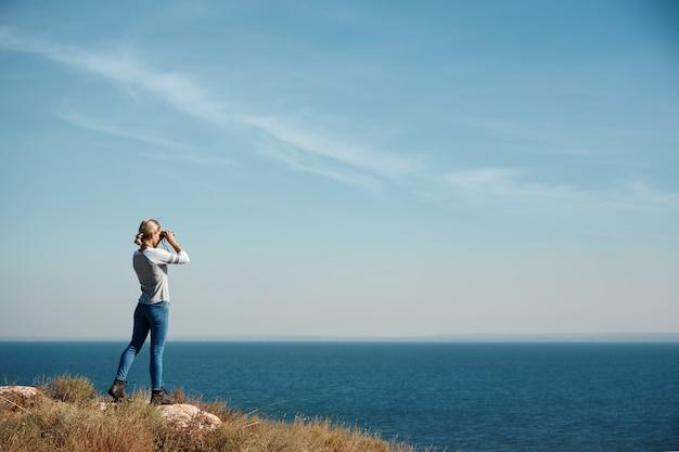 Женщина смотрит в бинокль