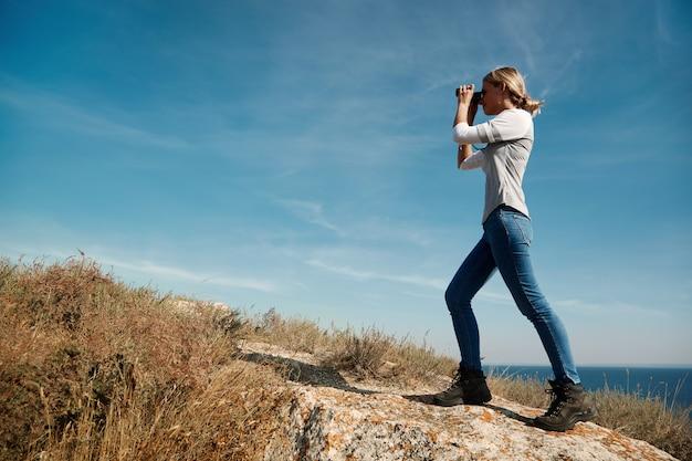 Donna che osserva tramite il binocolo
