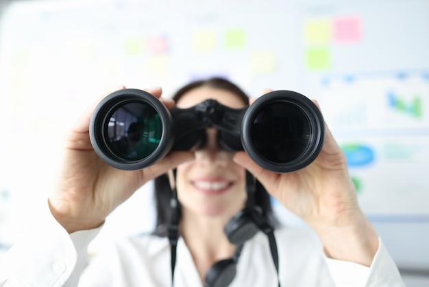 Женщина смотрит в черный бинокль в офисе крупным планом Premium Фотографии