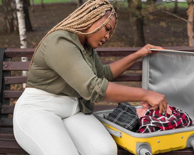 Женщина, просматривающая открытый багаж
