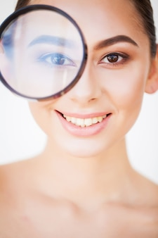 Woman looking through magnifier and smiling close up.