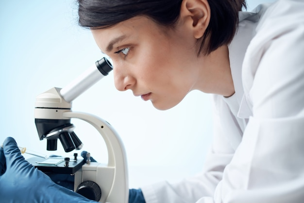Woman looking through a microscope diagnostics science research closeup