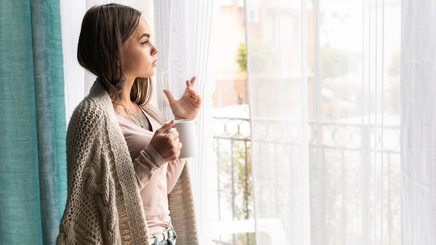Woman looking through the window at home during the pandemic while having coffee