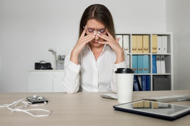 Donna che sembra stanca al lavoro a causa del tempo trascorso al telefono