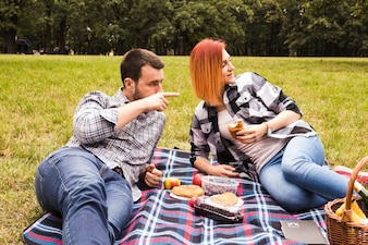 Woman looking to her boyfriend pointing at something enjoying at picnic in park
