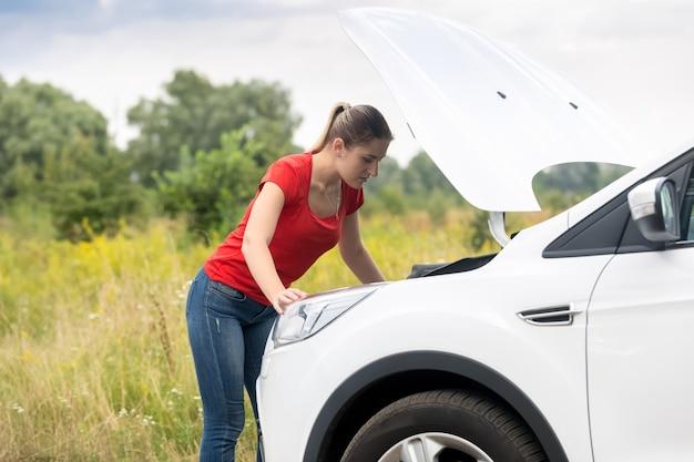 牧草地で過熱した車のボンネットの下で見ている女性