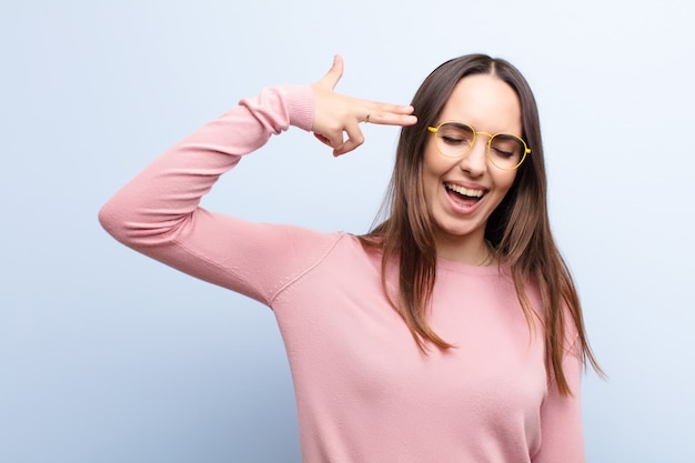 Woman looking unhappy and stressed, suicide gesture making gun sign with hand, pointing to head